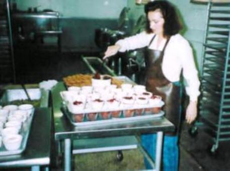 Jeanine Durand Arnopoulos prepping for lunch while in the background a display steam jacketed 40 gallon cookers line the back wall.
