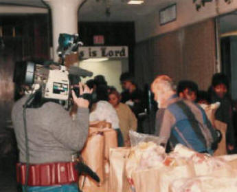 Holiday GiveAway Pastor Paul S Arnopoulos distributes groceries while TV stations record the event.