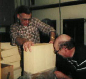 Church volunteers cut 40 pound blocks of frozen cheese into 1 pound chunks using a wire.