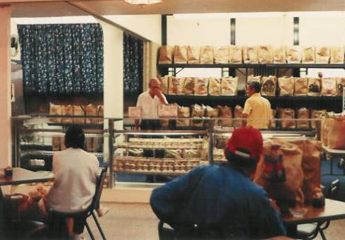 Glass bakery display cases line the front of Pastor Paul's Mission Grocery Shelf 1986.