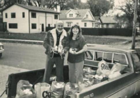 Pastor Paul and Judy, a member of the church, collect canned food for the 1st FoodDrive for the Grocery Shelf in 1983.