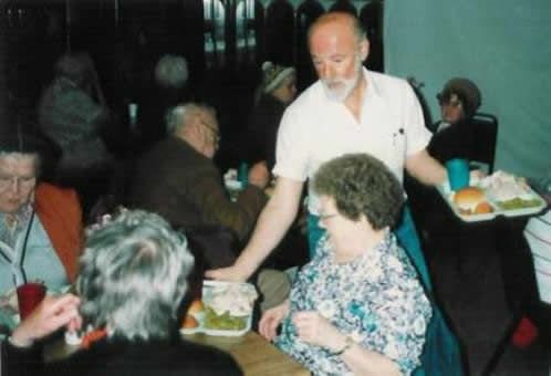 Pastor Paul S Arnopoulos serving lunch to seniors on Senior's Day.