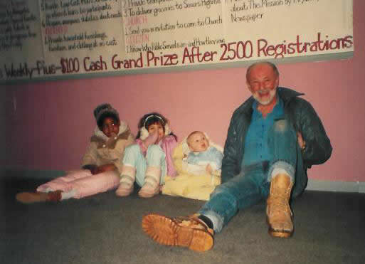 Pastor Paul S Arnopoulos with small children sittiing on the floor in 1985.