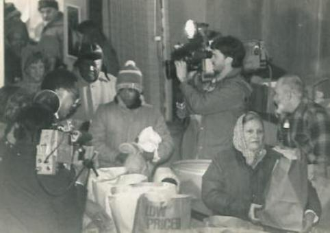 The TV cameras are recording the lines of people at the Thanksgiving GiveAway in 1984.
