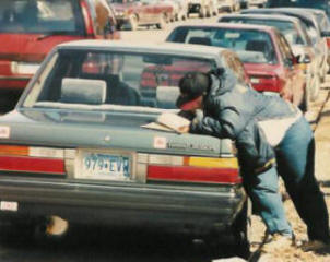 A very focused woman is filling out the survey on her car.